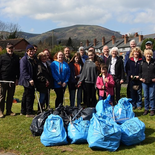 A group of people stand behind a large pile of big bags full of litter they've collected
